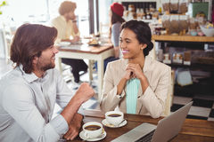 Smiling man and woman using a laptop while having cup of coffee Royalty Free Stock Images