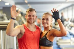 Smiling man and woman waving hands in gym Royalty Free Stock Photos