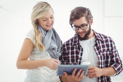 Smiling man and woman working on digital tablet stock images