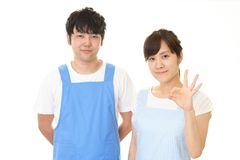 Smiling man with woman. Young people wearing apron isolated on white background royalty free stock images