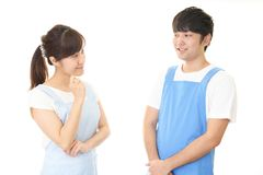 Smiling man with woman. Young people wearing apron isolated on white background stock image