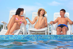 Smiling man and women reclining on chaise lounges Stock Photo