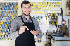 Smiling man worker showing key in workshop. Smiling man worker showing key he made in repair workshop Stock Photo