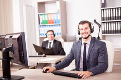 Smiling man working at Customer service support in the office Royalty Free Stock Image