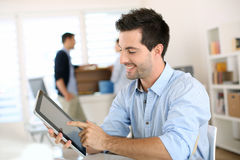 Smiling man working with a digital tablet Royalty Free Stock Images