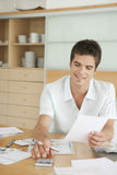 Smiling Man Working on Finances. Hispanic man working on his home finances in the kitchen Royalty Free Stock Photo