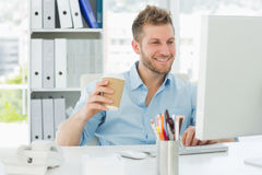 Smiling man working at his desk drinking a take away coffee Stock Images