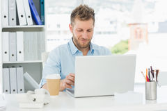 Smiling man working at his desk on laptop Royalty Free Stock Photo