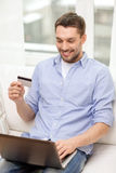 Smiling man working with laptop and credit card Stock Photos