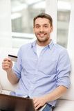 Smiling man working with laptop and credit card Royalty Free Stock Images
