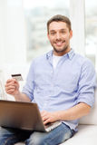 Smiling man working with laptop and credit card Stock Photo