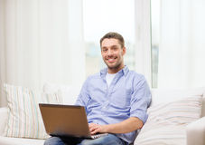 Smiling man working with laptop at home Royalty Free Stock Photo