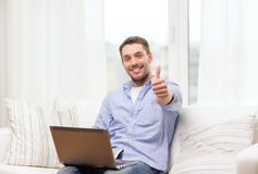 Smiling man working with laptop at home Royalty Free Stock Photography