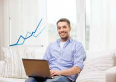Smiling man working with laptop at home Stock Image