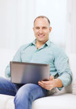 Smiling man working with laptop at home Stock Photos
