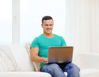 Smiling man working with laptop at home. Technology, home and lifestyle concept - smiling man working with laptop at home stock photos