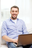 Smiling man working with laptop at home Stock Photography