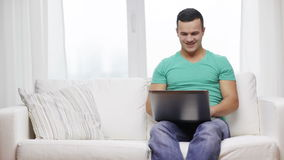 Smiling man working with laptop at home stock footage
