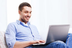 Smiling man working with laptop at home Royalty Free Stock Photos