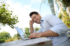 Smiling man working on laptop outdoors Stock Photo