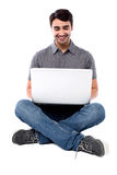 Smiling man working on laptop. Smiling young guy sitting on the floor with laptop Royalty Free Stock Photos