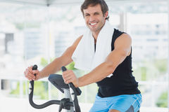 Smiling man working out at spinning class in bright gym Royalty Free Stock Photography