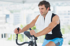Smiling man working out at spinning class in bright gym Royalty Free Stock Photos