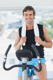 Smiling man working out at spinning class in bright gym Stock Image