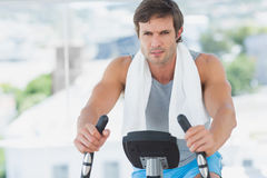 Smiling man working out at spinning class in bright gym Stock Images