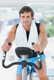 Smiling man working out at spinning class in bright gym Royalty Free Stock Images