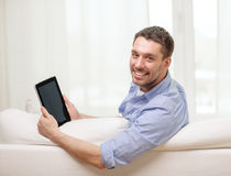 Smiling man working with tablet pc at home Royalty Free Stock Images