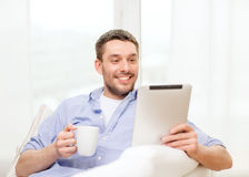 Smiling man working with tablet pc at home. Technology, home and lifestyle concept - smiling man working with tablet pc computer and coffee cup at home stock photography