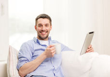 Smiling man working with tablet pc at home. Technology, home and lifestyle concept - smiling man working with tablet pc computer and coffee cup at home stock image