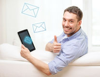 Smiling man working with tablet pc at home. Technology, home and lifestyle concept - smiling man working with tablet pc computer at home showing thumbs up royalty free stock images