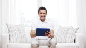 Smiling man working with tablet pc at home stock video footage