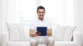 Smiling man working with tablet pc at home stock video