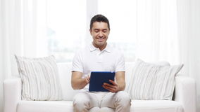 Smiling man working with tablet pc at home stock footage