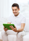 Smiling man working with tablet pc at home Royalty Free Stock Photos