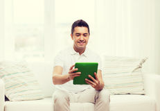 Smiling man working with tablet pc at home Royalty Free Stock Image