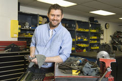Smiling Man In Workshop With Tools. Portrait of a smiling young man with tools working in workshop Royalty Free Stock Images