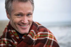 Smiling man wrapped in shawl at the beach stock photo