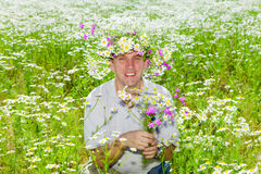 The smiling man in a wreath from wild flowers Royalty Free Stock Images