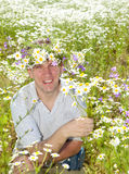 The smiling man in a wreath from wild flowers in the field of camomiles Stock Photography