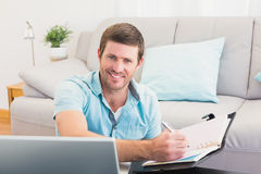 Smiling man writing on a notebook Royalty Free Stock Images