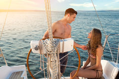 Smiling man beside yacht wheel. Smiling men beside yacht wheel. Girl and guy on boat. Let me tell you something. Don't be shy Royalty Free Stock Photos
