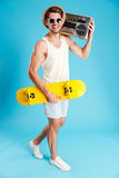 Smiling man with yellow skateboard walking and holding old boombox. Smiling young man with yellow skateboard walking and holding old boombox Royalty Free Stock Photo