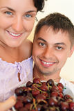 Smiling man and young woman eat cherries Stock Image