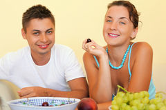 Smiling man and young woman eat fruit in cosy room Royalty Free Stock Photos