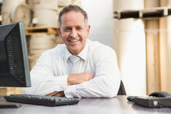 Smiling manager with arms crossed sitting at desk Stock Images