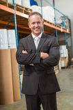 Smiling manager with arms crossed in warehouse Royalty Free Stock Images